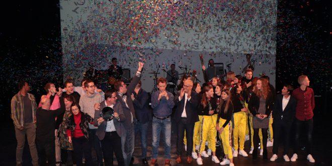 Alle winnaars met hun prijs op het podium.