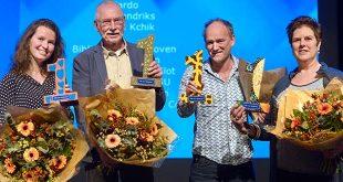 De vier vertegenwoordigers van de winnende stichtingen met hun prijs en een bos bloemen.