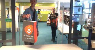 Mark en Maya van de bibliotheek delen met plezier boekenpakketten uit